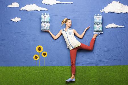 junge Frau balanciert auf Hand und Fuß Wasserflaschen