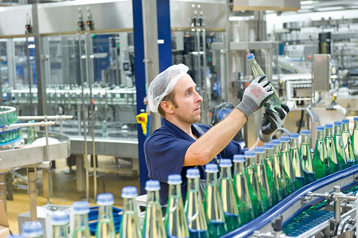A man is checking the condition of a glass bottle on the production site